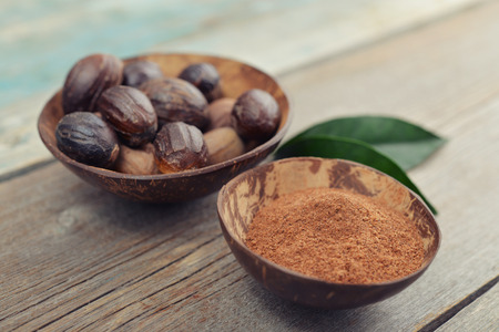Group of nutmegs (seeds of Myristica fragrans), whole and ground in bowls on wooden background