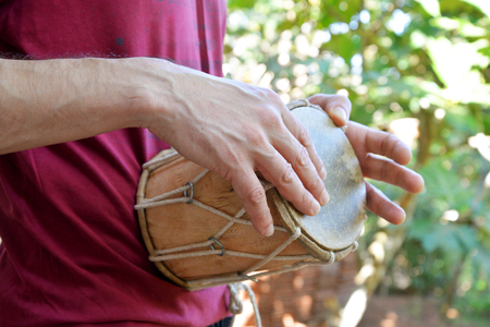 djembe drum: Man playing on traditional Indian drum djembe outdoor closeup Stock Photo