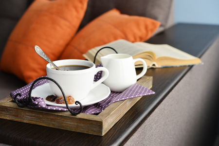 Cup of coffee on vintage tray on sofa with open book.