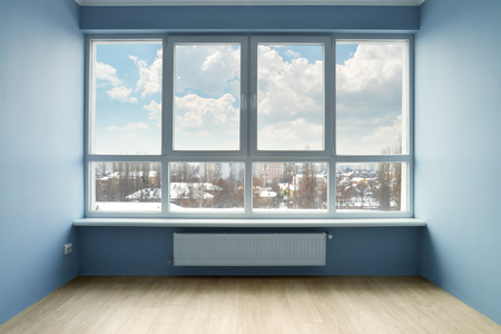 Empty room with large window and blue walls