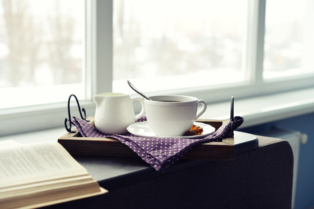 windowsill: Cup of coffee on vintage tray on sofa with window on background Stock Photo