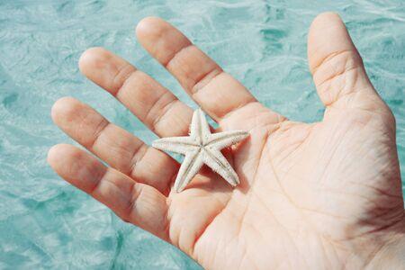 persona viajando: Hombre que sostiene las estrellas de mar en las manos sobre fondo del mar Foto de archivo