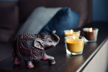 homelike: Handcrafted indian elephant and candles on an wooden table in home interior closeup