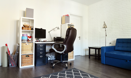 Home office interior with laminate floor and simple furniture. Stock Photo