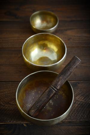 massage symbol: Tibetan handcrafted singing bowls with sticks on wooden background