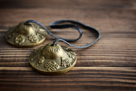 Tibetan Ting Sha Ceremonial Bells on wooden background closeup Stock Photo