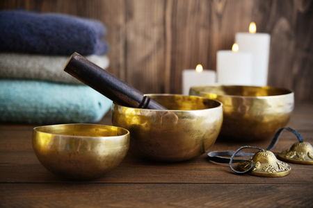 Tibetan handcrafted singing bowls with towels and candles on wooden background Stock Photo