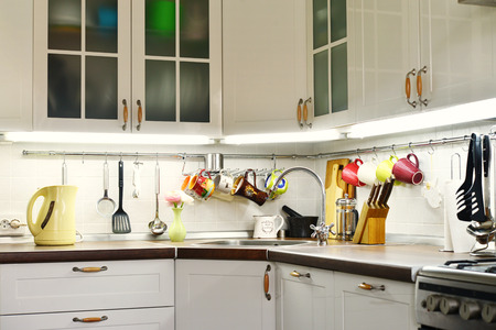 A fragment of the Scandinavian style kitchen with rail system and kitchen utensils
