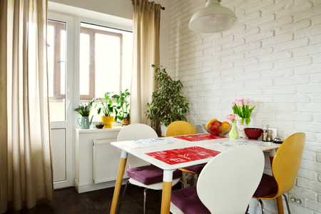 furnishings: Interior of the kitchen in Scandinavian style with white furniture and a dining table Stock Photo