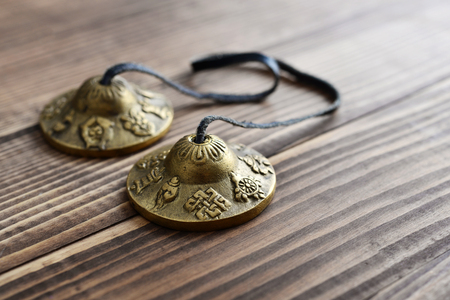 resonate: Tibetan Ting Sha Ceremonial Bells on wooden background closeup Stock Photo