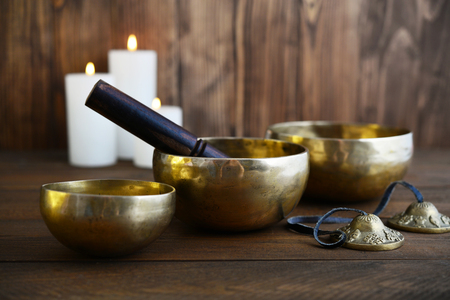 Tibetan handcrafted singing bowls with sticks on wooden background