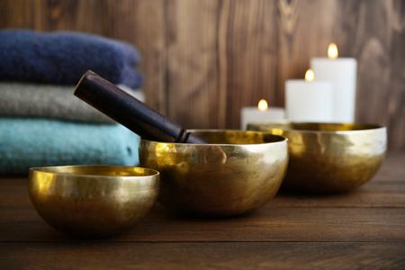 Tibetaanse handgemaakte zangbakken met handdoeken en kaarsen op houten achtergrond Stockfoto