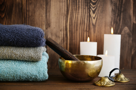 tibetan singing bowl: Tibetan handcrafted singing bowls with towels and candles on wooden background Stock Photo