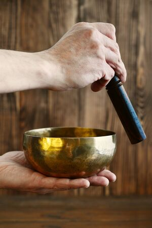 Male hand playing on Tibetan handcrafted singing bowls on wooden background