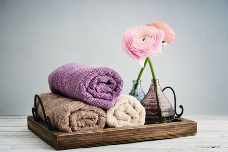 Folded towels with ranunculus in vases on blue background Stock Photo