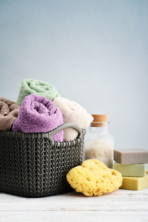 Bath towels of different colors in wicker basket with soap bars and sponge on light background