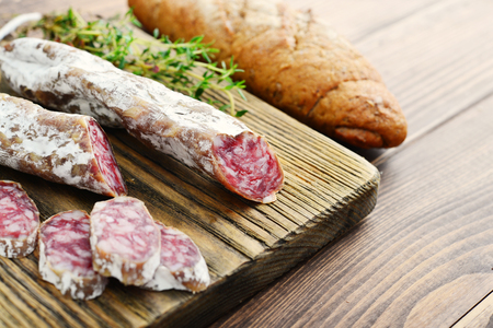 Spanish moldy salami on cutting board with olives and bread over wooden background