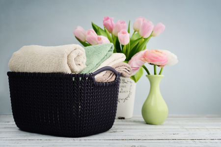 Bath towels of different colors in wicker basket with tulips in vase on light background Stock Photo