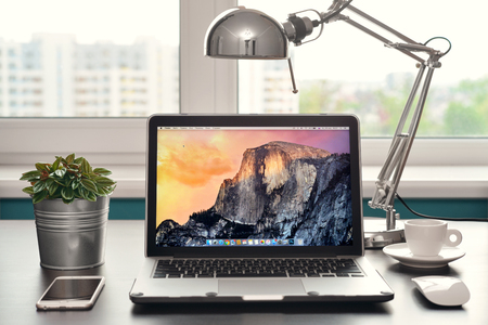 KIEV, UKRAINE - April 30, 2017: Apple MacBook Air Early 2014, designed and developed by Apple Inc. with computer mouse and Rose Gold iPhone 6S on black table.