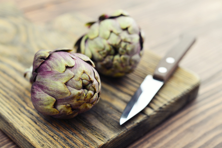 Two fresh artichokes with stem  on wooden background closeup Stock Photo