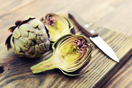 Two fresh artichokes with stem and a half showing the heart on wooden background closeup Stok Fotoğraf - 78569772