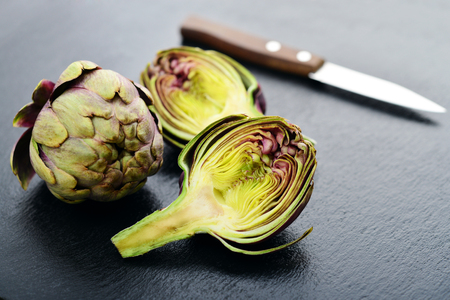 Two fresh artichokes with stem and a half showing the heart on slate background closeup Stock Photo