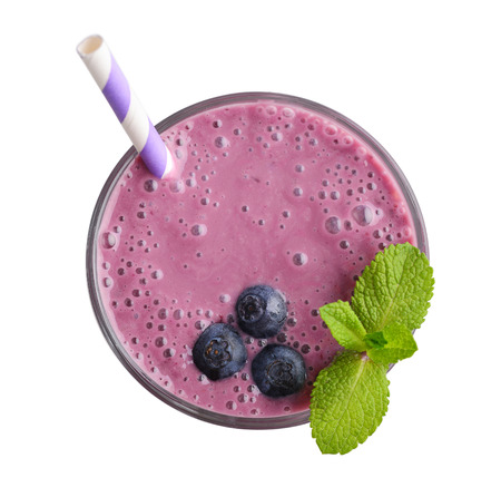 Glass of blueberry milkshake or smoothie with drinking straw and mint leaves  isolated on white background, top view