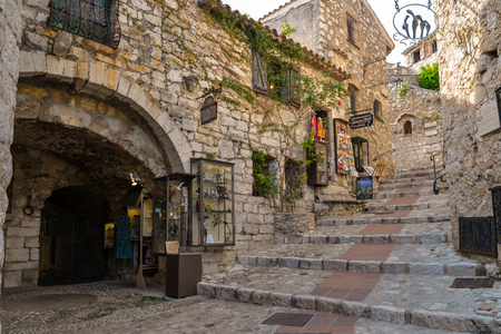 EZE, FRANCE -  April 12, 2017: The narrow hilly street with tourist shops and cafes, located in medieval stone houses in Eze, France.