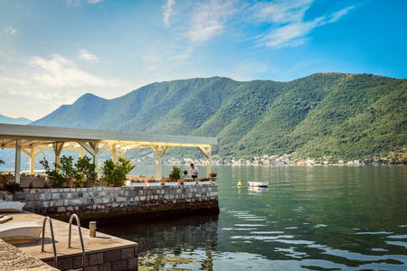 balkans: The old cafe on the water is the favorite tourist place with delicious local cuisine and nice view on Kotor bay, Perast, Montenegro. Stock Photo