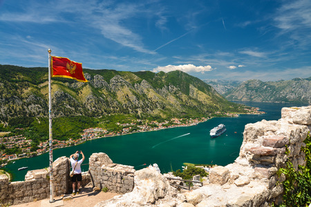 The national flag of Montenegro and the view on Kotor bay from Lovcen Mountain. Montenegro.