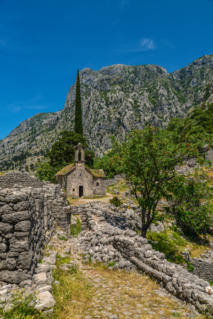 balkans: Ancient Serbian church ruins and mountain valley landscape near Kotor castle fortress wall in Montenegro. Stock Photo