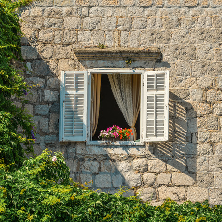 louvered: A typical montenegrian window with louvered shuters and  flowers in hanging flower pots Stock Photo