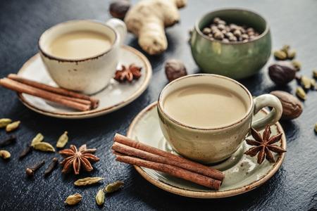 Traditioneel Indisch drankje - Masala Chai thee (Melkthee) Met Kruiden op zwarte leisteenachtergrond Stockfoto - 83473151