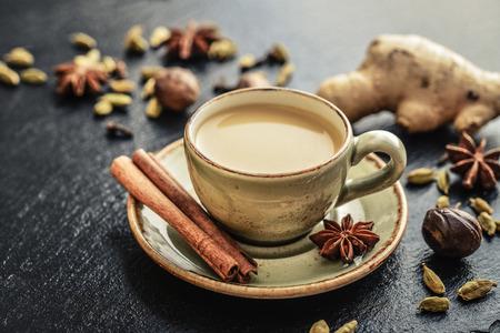 Traditioneel Indisch drankje - Masala Chai thee (Melkthee) Met Kruiden op zwarte leisteenachtergrond