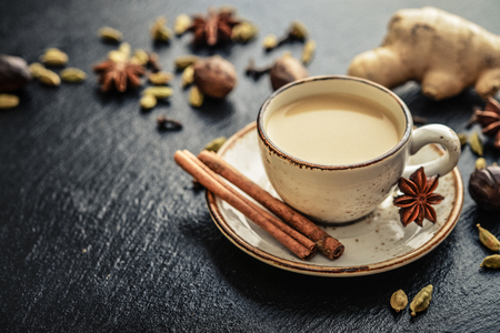 Traditional indian drink - masala chai tea (milk tea) with spices on black slate  background