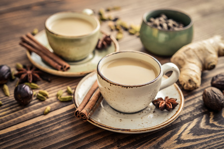 Traditional indian drink - masala chai tea (milk tea) with spices on wooden background