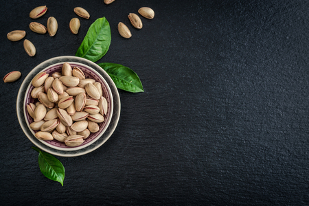 Pistachios in shell on blue plate over black slate background, top view