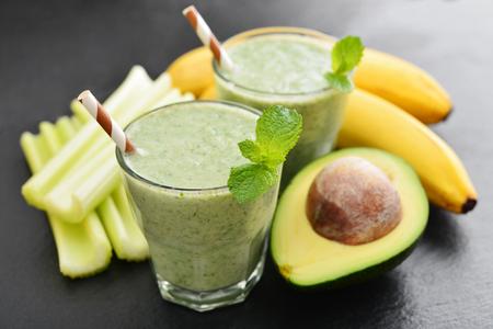 Verse avocado smoothie met limoen en selderij op zwarte leisteen achtergrond