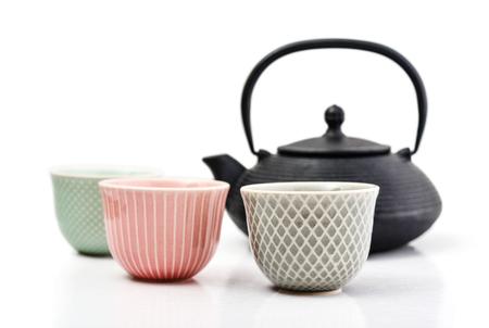 鋳鉄製のティーポットと明るい背景に小さなカップで緑茶