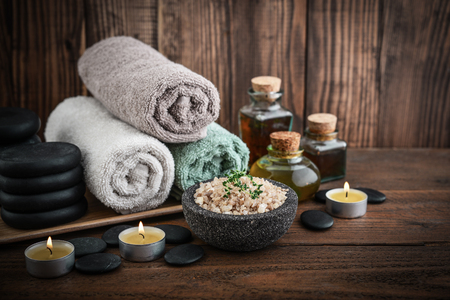 Towels with sea salt, massage oil in vintage bottle, candles and stones for stone massage on wooden background
