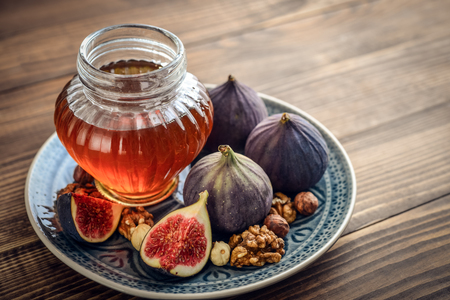 stirrer: Honey with fresh figs and nuts on wooden background closeup