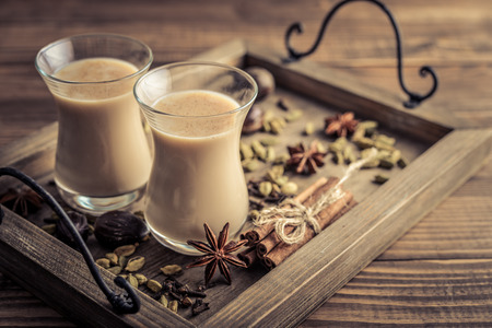 Traditional indian drink - masala chai tea (milk tea) with spices on a wooden background
