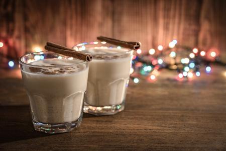 Traditionele kerst drankje advocaat in glas met specerijen en KERSTVERLICHTING op houten achtergrond