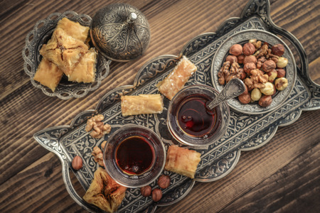 Cup of turkish tea served in traditional style with turkish delight on wooden background, top view Stock Photo