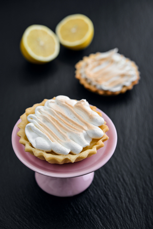 Tartlet with Italian meringue and lemon curd on a cakes stand on black slate background closeup