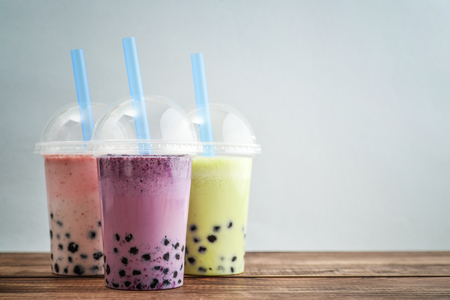Various Bubble Tea in a plastic cups with drink straws on blue background. Take away drinks concept. Stock Photo