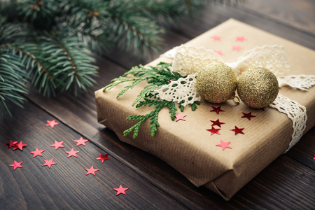 Christmas gift with fir tree twig on wooden background