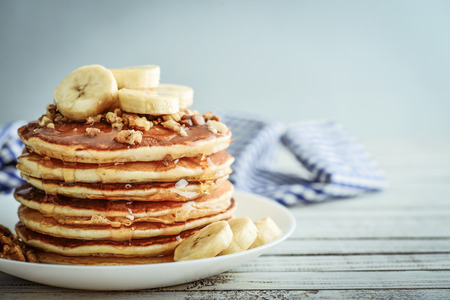Pancakes with banana,walnut and muple syrup for a breakfast on wooden background closeup