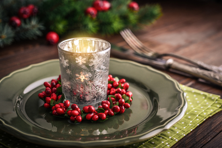 Christmas Table Setting with Holiday Decorations and candles on wooden table closeup