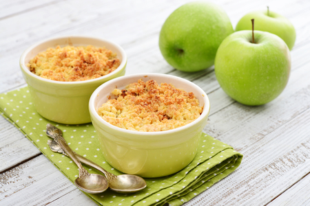 Apple crumble in small baking dish with fresh apples on wooden background